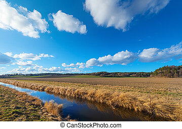 Farmland with irrigation canal during a sunny day in spring...