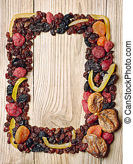 Decorative frame with dried fruits on wooden table