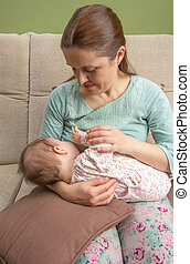 Young mother breast feeding her baby at home