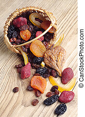 Dried fruits in a wicker basket and near on a wooden table