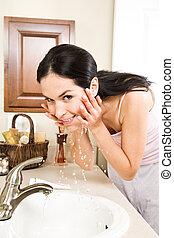 Woman washing face - A beautiful hispanic woman washing her...