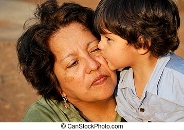 Grandmother and grandson - grandson giving a kiss to his...