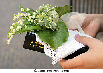confirmation - Hands of a Girl with flowers and hymn-book