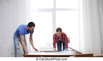 smiling couple opening big cardboard box - repair, building...