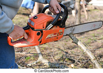 A man is using an orange chainsaw to cut tree branches lying...