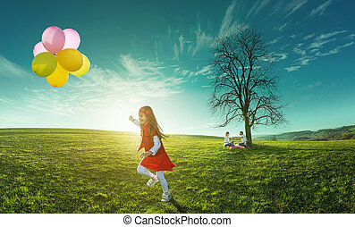 Happy girl running in a meadow with colorful balloons on a background of parents