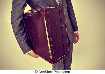 man in suit with an old suitcase - a man wearing a suit with...