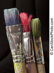 three paintbrushes in different colors - parts of...