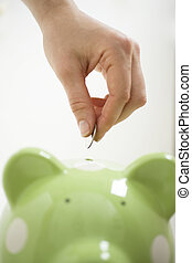 Motivated to save  - Hand placing coin in green piggy bank