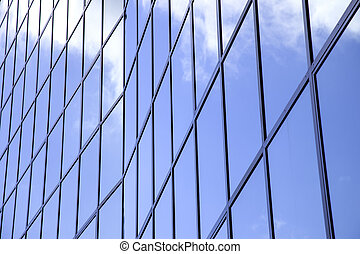 reflexions of clouds and blue sky in facade of modern...