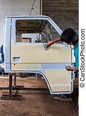Preparing the body of a car for a repair job - Mechanic...