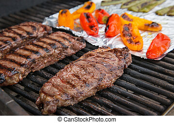 Steaks cooking on the grill. Colorful peppers on foil on the...