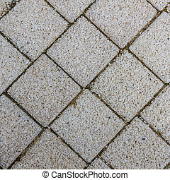 Paving slabs in the form of squares. Small gravel surface.