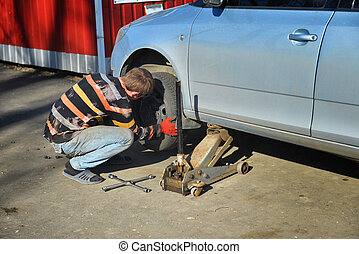 Man changing tires on the car at the service station