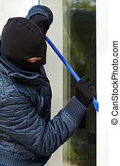 Fighting with window - A masked burglar trying to open the...