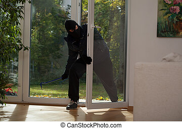 Balcony window burglary - A burglar entering a house through...