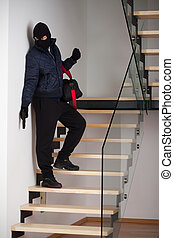 Criminal on staircase - A criminal with a bag standing on a...