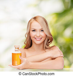 happy woman with oil bottle - health and beauty concept -...