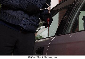 Car break-in closeup - A close-up of a man trying to break...