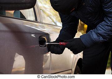 Opening car door - A burglar opening car's door by breaking...