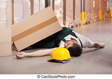 Accident in warehouse - Young male worker lying on the floor...