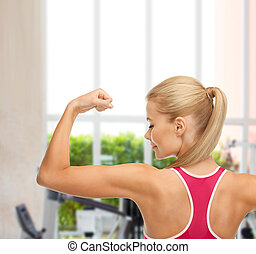 sporty woman showing her biceps - fitness and gym concept -...