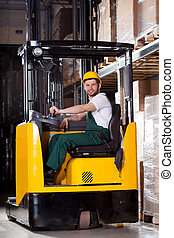 Smiling forklift driver - Smiling male worker in yellow...