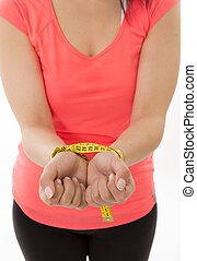 woman's hands handcuffed together with a measuring tape - a...