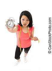 asian woman worried about starting a diet holding alarm...