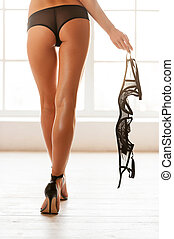 Taking off her bra. Cropped rear view image of beautiful young woman in black panties walking with bra in her hand