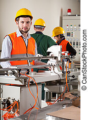 Workers in factory - Three workers in uniforms and safety...