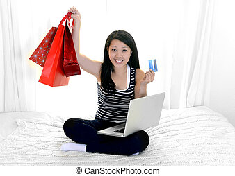 asian american woman with credit card and shopping bags