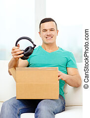 opening cardboard box and taking out headphones - post,...
