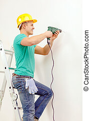 man with electric drill making hole in wall - repair,...
