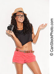 Funky girl with camera. Cheerful young African woman in...