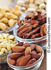 Bowls of nuts - Almonds, cashews pistachio and pine nuts in...