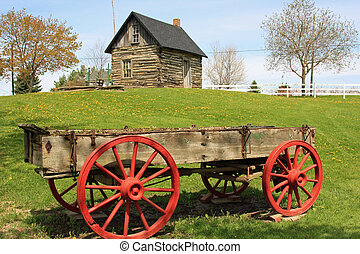 Pioneer log cabin and wooden wagon in rural Michigan