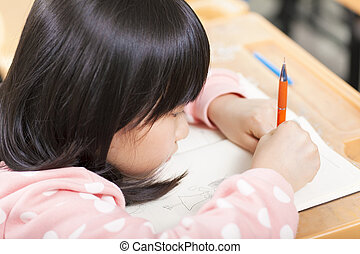 student is focus on drawing his book