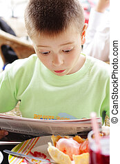 Very unexpected article - Boy reading paper in cafe with...