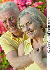 Loving elder couple sitting on a background of flowers
