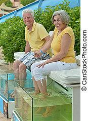 couple at fish spa skin treatment - Senior couple at fish...