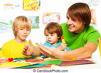 Happy father teaching kids to craft - Father and little boys...