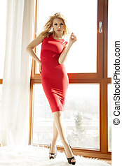 Young slim sexy woman in red dress against the window