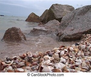 sea coast with stones and small soft waves