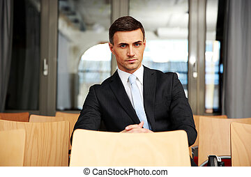 Confident businessman sitting at conference hall