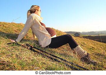 Pregnant woman heaving a break during a walk