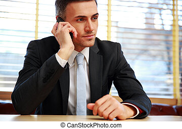 Confident businessman sitting and talking on the phone at...