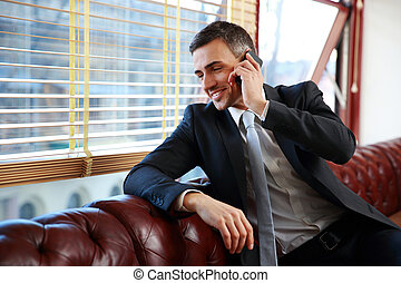 Happy businessman talking on the phone and looking in window...