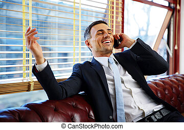 Laughing businessman sitting and talking on the phone at...