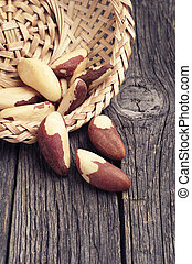 Brazil nuts in wicker bowl and near on wooden surface